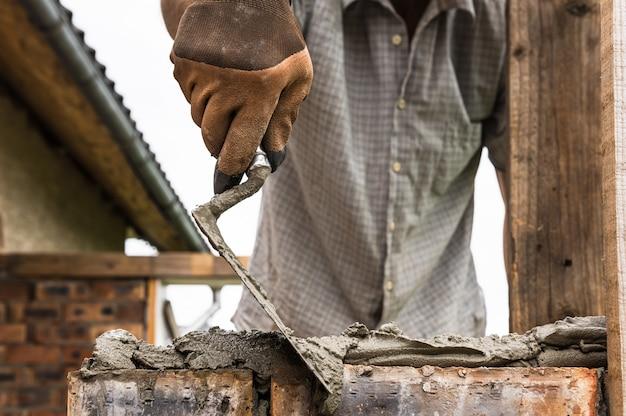 Рабочий, наносящий раствор мастерком на кирпич