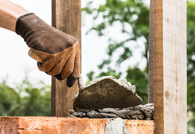 Worker applying a mortar with a trowel to the brick
