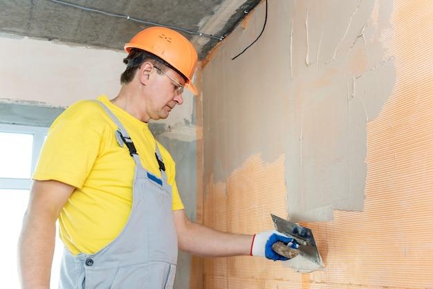 Рабочий, наносящий шпатлевку на сетку из стекловолокна на стене