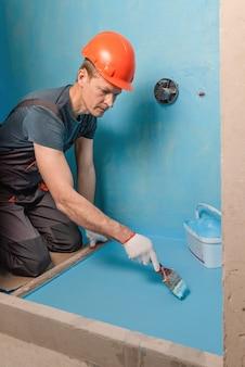 Рабочий, наносящий гидроизоляционную краску на пол в ванной комнате