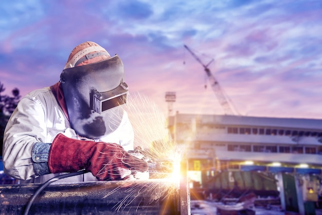 Worker arc welder piping welding buiding in shipyard background soft monoto