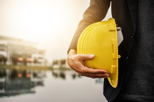 Рабочий-инженер-архитектор держит каску для безопасности при строительстве