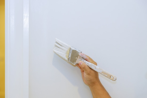 작업자는 집 내부를 개조하는 흰 벽에 도어 트림 몰딩에 그림을 그리고 있습니다.