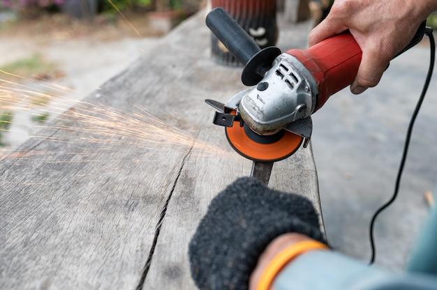 労働者は電気のこぎりと輝きで刃のシャベルを研いでいます