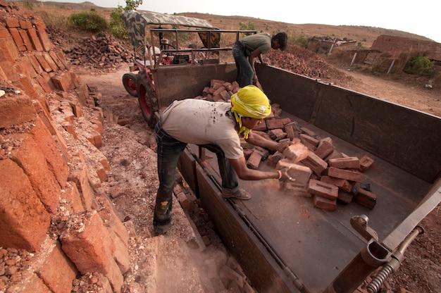 労働者はレンガ工場で次のプロセスのためにレンガを配置します