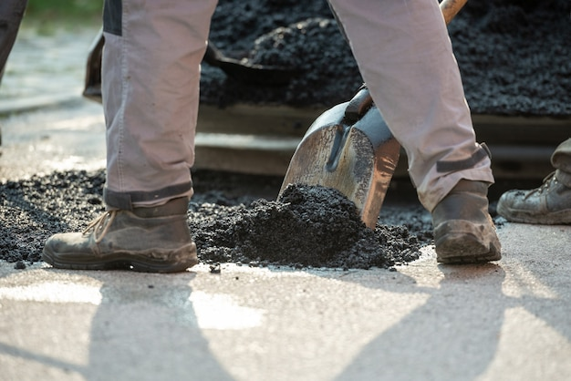 Worker arranging fresh asphalt mixture with shovel to patch a bump in the street.