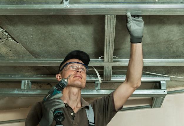 Рабочий собирает профиль металлический каркас