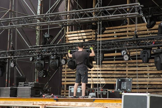 Рабочий собирает осветительное оборудование мобильной сцены.