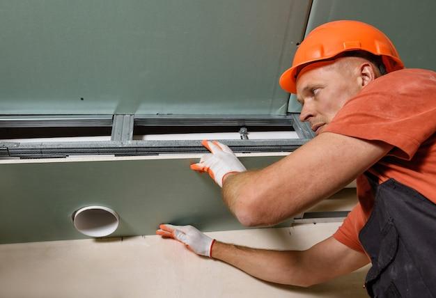 Рабочий, монтаж гипсокартона с вентиляционным отверстием
