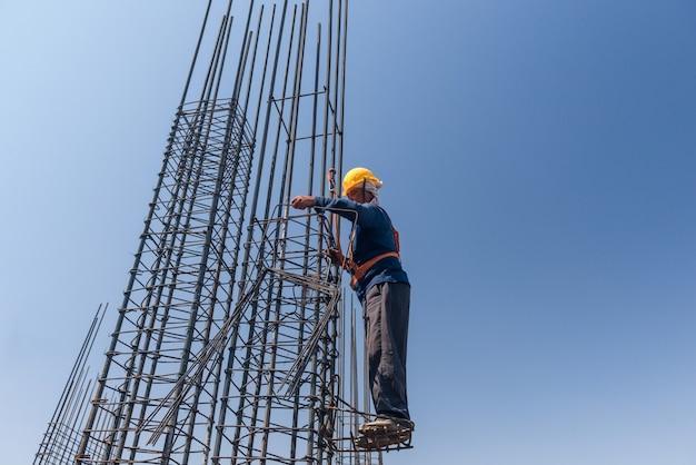 고도에 있는 작업자는 푸른 하늘 배경에 있는 철근의 기둥을 강화합니다. 실제 사람들