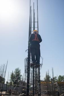 고도에 있는 작업자는 푸른 하늘 배경의 철근에서 기둥을 강화합니다