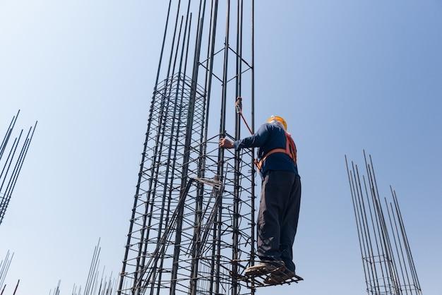 Рабочий на высоте укрепляет столбы из арматуры на фоне голубого неба.