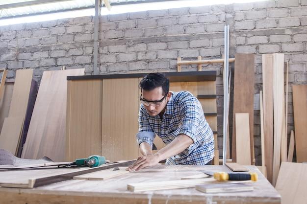 Рабочий в столярной мастерской рубит доску с помощью пилы