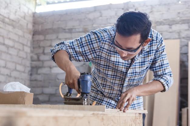 Рабочий на столярной мастерской укладывает гвоздь с помощью пневматического гвоздя