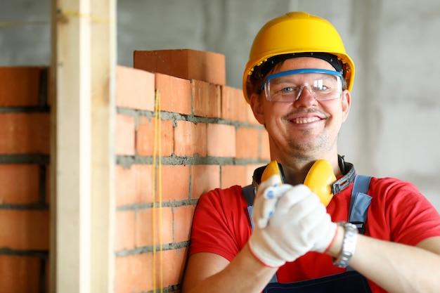 Работник на строительной площадке, делая жест дружбы в защитные перчатки выстрел в голову