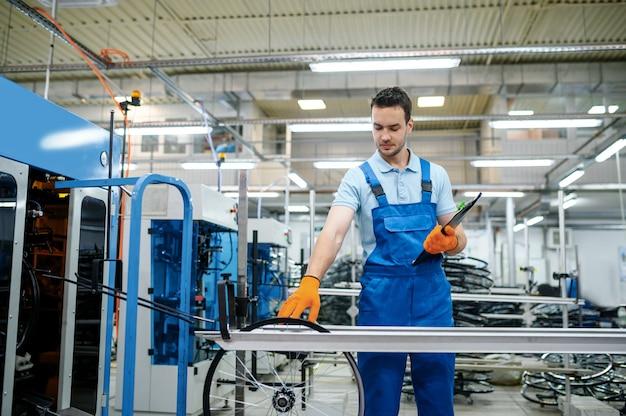조립 라인의 작업자가 공장에서 자전거 바퀴를 확인합니다. 작업장에서 자전거 림 및 스포크 생산, 사이클 부품 설치, 현대 기술