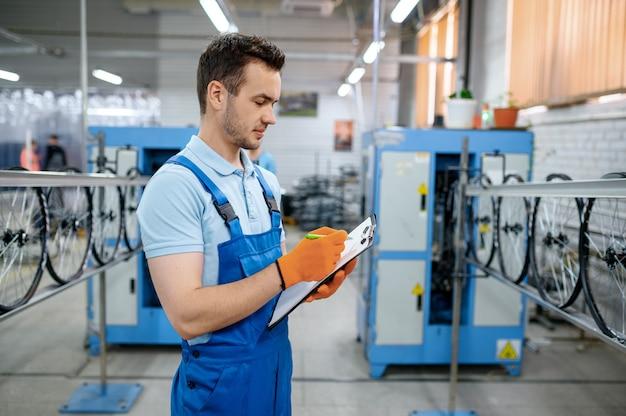 조립 라인의 작업자가 공장에서 자전거 바퀴를 만듭니다. 작업장에서 자전거 림 및 스포크 생산, 사이클 부품 설치