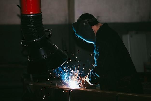 Рабочий на заводе в каске из железа в процессе сварки яркие искры