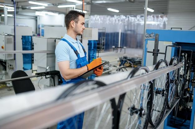 공작 기계의 작업자가 공장에서 자전거 테두리를 만듭니다. 작업장에서 자전거 바퀴 조립, 사이클 부품 설치
