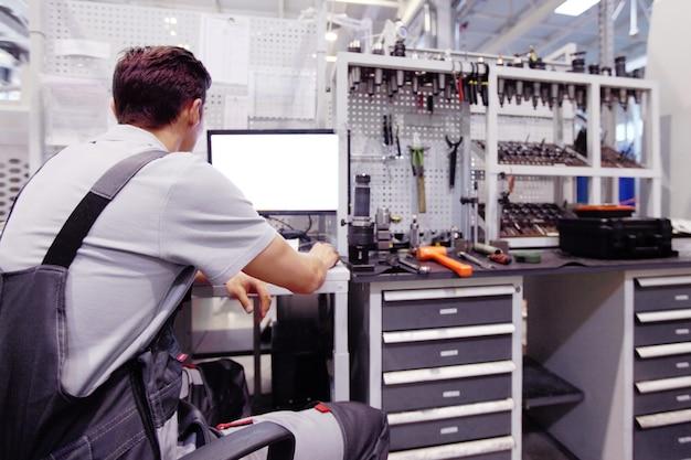Рабочий на рабочем месте с компьютером и инструментами на заводе с чпу