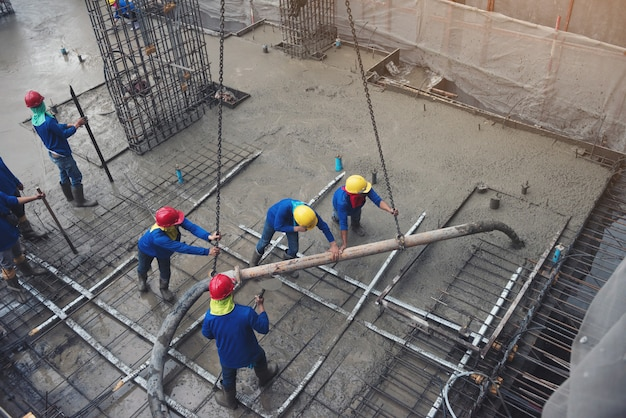 The worker in blue working in construction site with cement