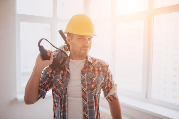 The worker or builder holds a cup of coffee in his hands and looks at the tablet