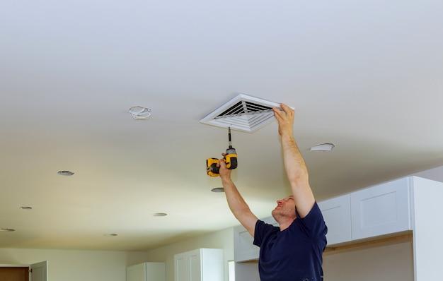 Рабочий строитель устанавливает вентилируемые вентиляционные крышки конструкции здания