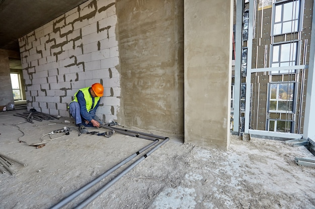Worker or builder in protective clothing and safety hard hat is installing plastic pipes using modern tools in a flat of building under construction