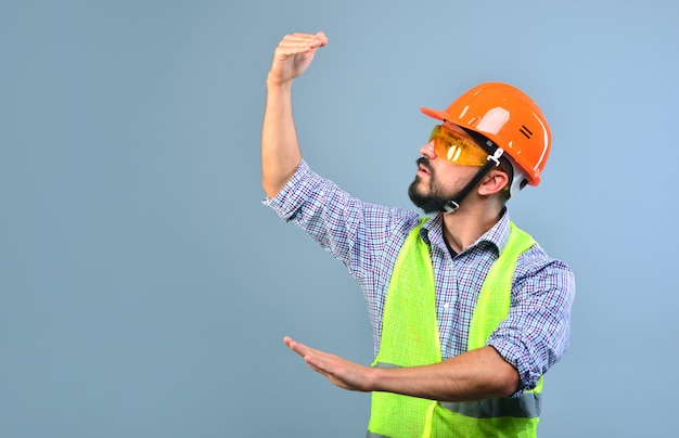 Рабочий-строитель в каске жестикулирует руками и наблюдает за зданием.