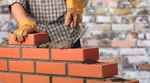 Рабочий строит кирпичную стену в доме