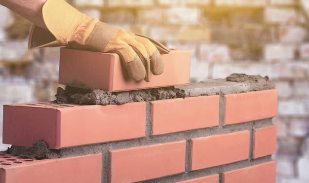 작업자가 집에 벽돌 벽을 만듭니다.