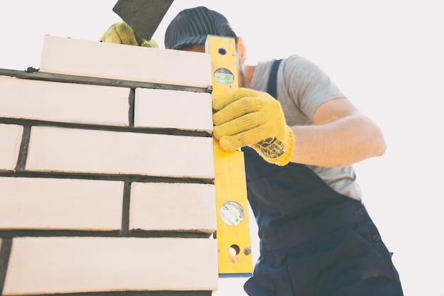 작업자는 벽돌로 울타리 기둥을 구축합니다.