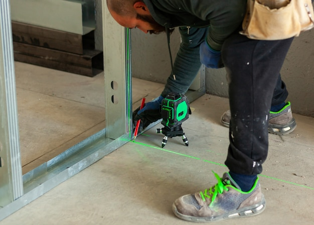 Worker builds a plasterboard wall