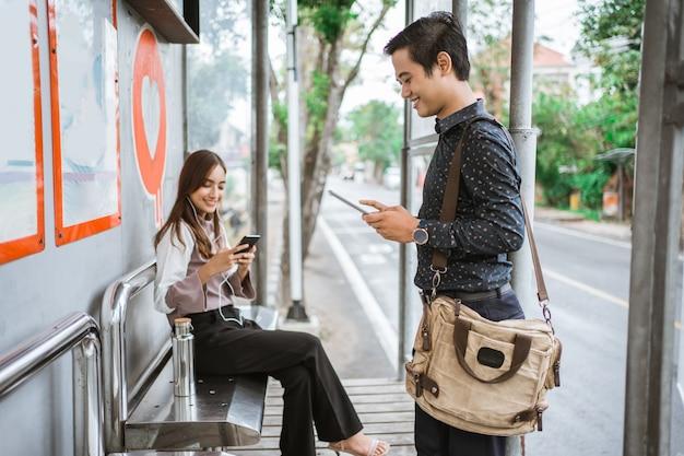 Работник занят с помощью своего гаджета в ожидании общественного транспорта