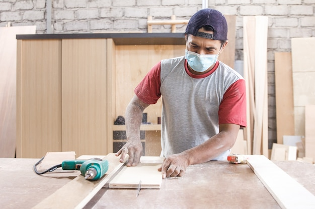 Worker at carpenter workspace cutting the wood board using saw