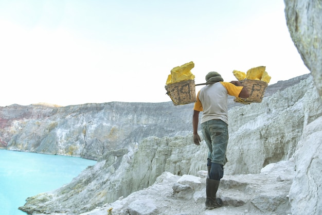 Worker carries sulfur (sulphur) inside kawah ijen volcano
