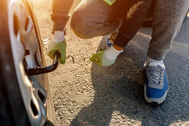 작업자는 자동차의 깨진 바퀴를 변경합니다. 운전자는 기존 휠을 스페어로 교체해야합니다