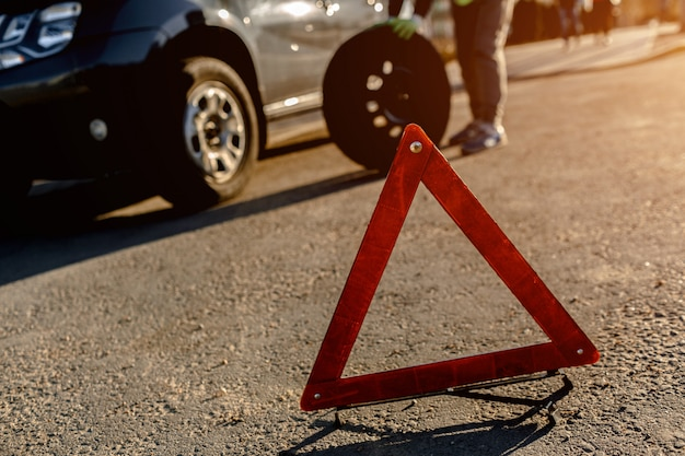 Worker changes a broken wheel of a car. the driver should replace the old wheel with a spare