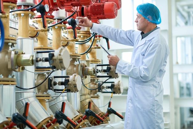 Рабочий проверяет трубы на современном заводе