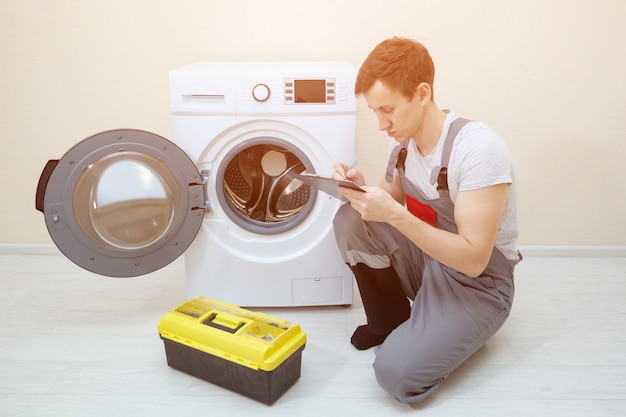 작업자는 깨진 세탁기를 확인하고 방에 메모를 합니다.