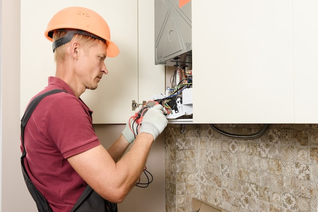 The worker checks the serviceability of the electronics of the gas boiler.