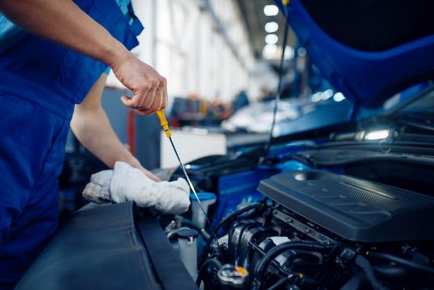 Рабочий проверяет уровень моторного масла, автосервис