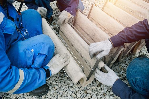 Рабочий, очищающий воздушный фильтр от порошка промышленного