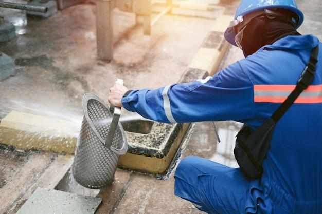Рабочий чистит сетчатый фильтр ведра на промышленном предприятии