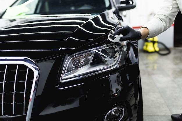 Рабочий, чистящий машину - концепция детализации (или очистки) автомобиля. выборочный фокус.