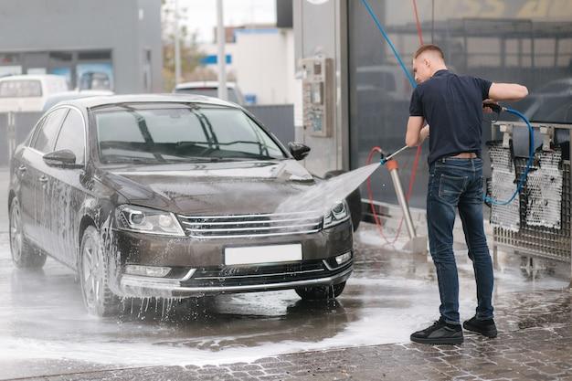 Рабочий чистит машину водой под высоким давлением.