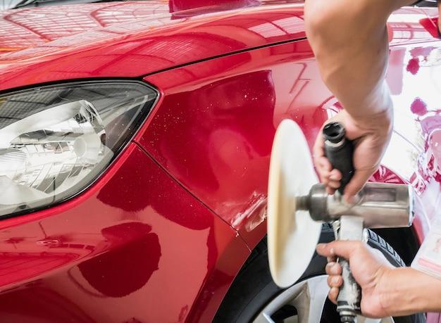 Рабочий, чистящий автомобиль с полировкой и воском красный автомобиль