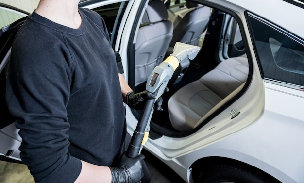 Worker cleans car interior with vacuum cleaner