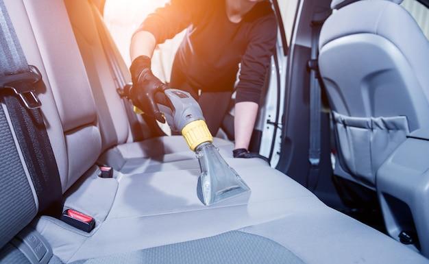 Рабочий чистит салон автомобиля пылесосом