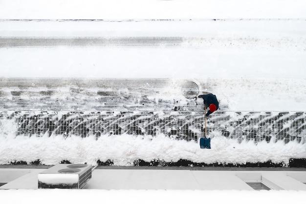 労働者はシャベルで雪をきれいにします